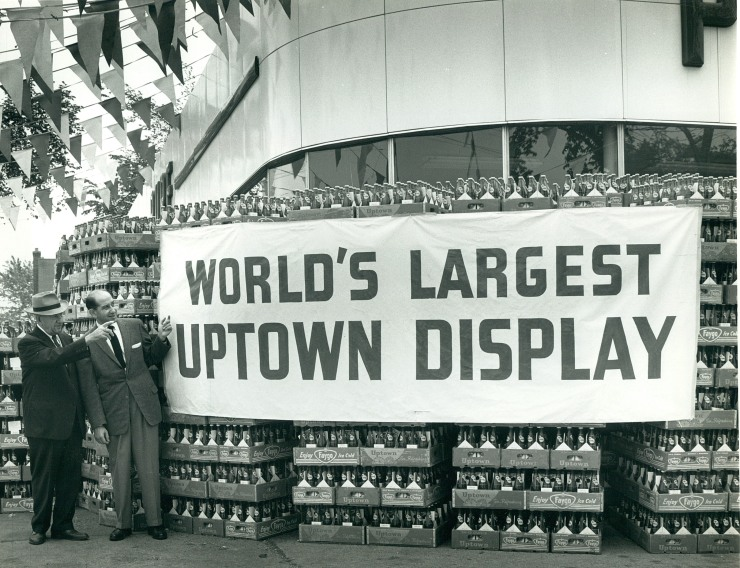 Two men in suits stand next to a tall and wide stack of cases of Uptown pop.
