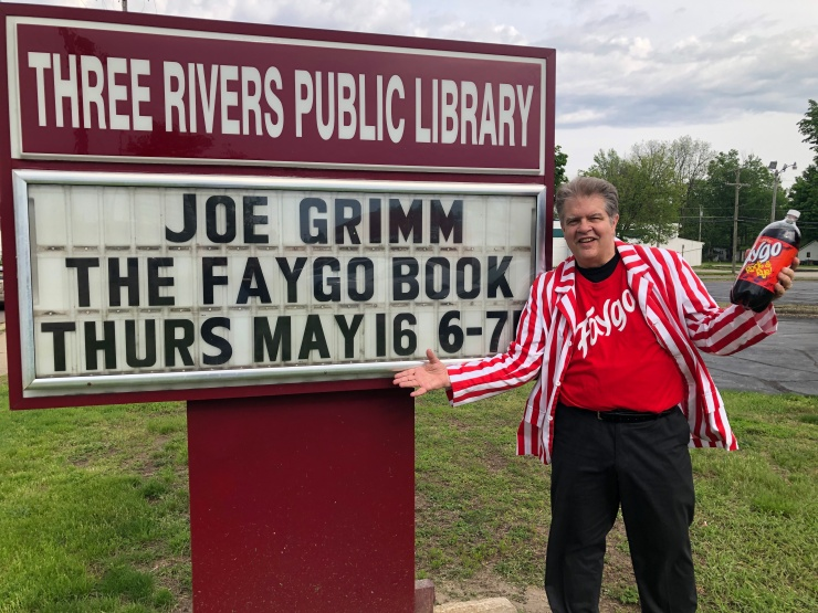 Th writer, in a Faygo shirt, stands in front of a roadside billboard that says Joe Grimm, The Faygo Book, Thursday, May 16, 6-7 p.m.