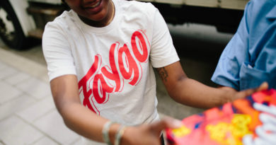 Man in a white T-shirt with a red Faygo logo holds a 12-pack of the pop.