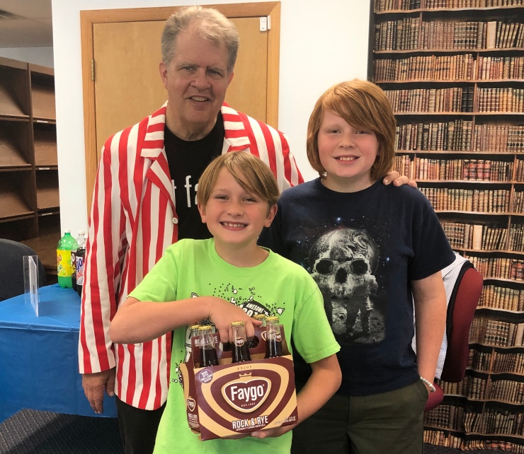 Two boys, one holding a six-pack of bottles, with book author.